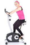 Woman exercising on training bicycle Royalty Free Stock Photo