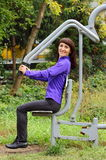 Woman exercising upper body on outdoor gym, healthy lifestyle Royalty Free Stock Image