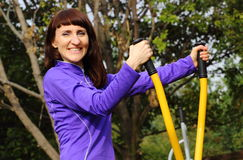 Woman exercising upper body on outdoor gym, healthy lifestyle Royalty Free Stock Images