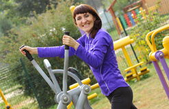 Woman exercising upper body on outdoor gym, healthy lifestyle Royalty Free Stock Photos