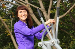 Woman exercising upper body on outdoor gym, healthy lifestyle Royalty Free Stock Photo