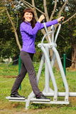 Woman exercising upper and lower body on outdoor gym, healthy lifestyle Royalty Free Stock Image