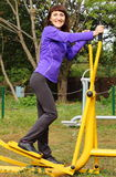 Woman exercising upper and lower body on outdoor gym, healthy lifestyle Stock Photo