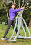 Woman exercising upper and lower body on outdoor gym, healthy lifestyle Stock Image