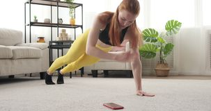 Woman exercising and using mobile phone at home. Woman getting distracted by mobile phone while exercising at home stock footage