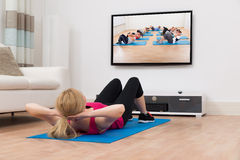Woman Exercising While Watching Television Stock Images