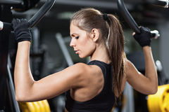 Woman exercising on weightlifting machine royalty free stock photography