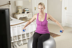 Woman Exercising Whilst Watching Fitness DVD On Television Stock Photos