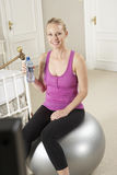 Woman Exercising Whilst Watching Fitness DVD On Television Royalty Free Stock Photos