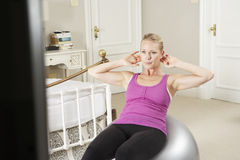 Woman Exercising Whilst Watching Fitness DVD On Television Stock Photography