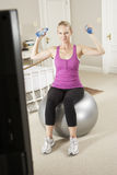 Woman Exercising Whilst Watching Fitness DVD On Television Royalty Free Stock Photo
