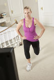 Woman Exercising Whilst Watching Fitness DVD On Television Stock Photo