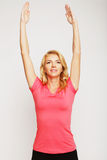 Woman exercising yoga with her arms over her head Stock Photos