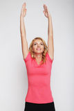 Woman exercising yoga with her arms over her head Stock Images