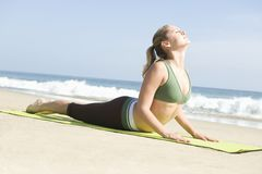 Woman Exercising On Yoga Mat At Beach. Young woman in sportswear practicing yoga on mat at beach Stock Photography