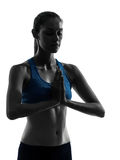 Woman exercising yoga portrait meditating hands joined silhouett Stock Images