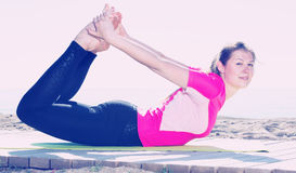 Woman exercising yoga poses on beach Royalty Free Stock Photo