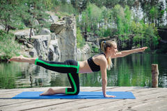 Woman exercising in yoga position while meditating at the lake Stock Photos