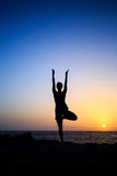Woman exercising yoga sunset silhouette. Young woman stretches yoga tree pose, sunset meditation silhouette in mountains. Motivation inspiration, sport and royalty free stock image