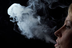 Woman exhaling smoke stock photo
