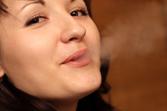 Woman exhaling smoke. Portrait of a young woman exhaling smoke Royalty Free Stock Images