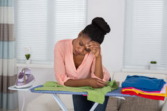 Woman Exhausted While Ironing Clothes Stock Photo