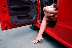 Woman exiting car. Leg of woman holding handbag exiting red car Royalty Free Stock Photography
