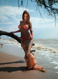 Woman in exotic dress standing on the beach. Beautiful woman in exotic dress standing on the beach. Sea ​​of ​​Azov stock photography