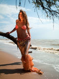 Woman in exotic dress standing on the beach Royalty Free Stock Photo