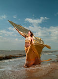 Woman in exotic dress standing on the beach Royalty Free Stock Image