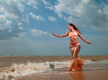 Woman in exotic dress standing on the beach Stock Photo