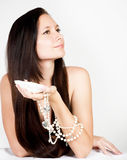 Woman with exotic shell and pearls Stock Photo