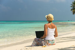 Woman on exotic tropical beach with laptop computer Royalty Free Stock Photos
