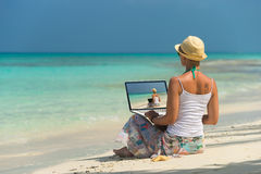 Woman on exotic tropical beach with laptop computer.  Stock Photography