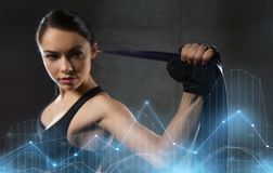 Woman with expander exercising in gym. Fitness, sport, training, people and lifestyle concept - woman doing exercises with expander or resistance band in gym Royalty Free Stock Photos