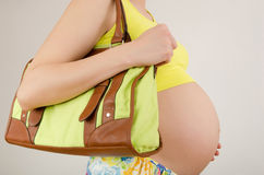 Woman expecting a baby holding a bag in her hands. Stock Photography