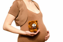 Woman expecting a baby holding a cute teddy bear. Royalty Free Stock Photo