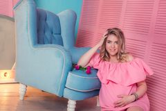 Woman expecting a baby in pink dress royalty free stock images