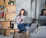 Female student chatting on cell telephone while sitting with modern net-book on windowsill royalty free stock image