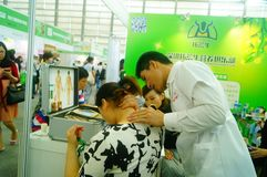 Shenzhen, China: health care exhibition, electronic acupuncture experience. A woman is experiencing the efficacy of electronic acupuncture apparatus at the stock photos