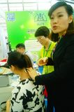 Shenzhen, China: health care exhibition, electronic acupuncture experience. A woman is experiencing the efficacy of electronic acupuncture apparatus at the stock photography