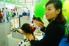 Shenzhen, China: health care exhibition, electronic acupuncture experience. A woman is experiencing the efficacy of electronic acupuncture apparatus at the royalty free stock images