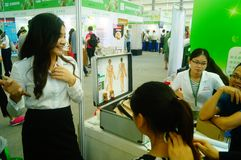 Shenzhen, China: health care exhibition, electronic acupuncture experience. A woman is experiencing the efficacy of electronic acupuncture apparatus at the stock photo