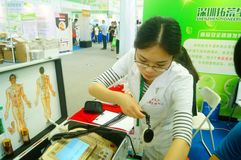 Shenzhen, China: health care exhibition, electronic acupuncture experience. A woman is experiencing the efficacy of electronic acupuncture apparatus at the royalty free stock photos