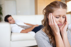 Woman experiencing headache. Young women experiencing headache with men on the sofa behind her Stock Images