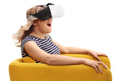Woman experiencing virtual reality. Young excited woman experiencing virtual reality seated in an armchair isolated on white background Stock Photo