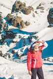 Woman explorer skier in mountains with snowy rocky background Stock Image