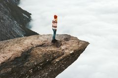Woman explorer walking on Trolltunga rocky cliff in Norway Royalty Free Stock Photo