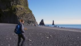 Woman exploring beautiful Reynisfjara beach near Vik, Icealnd stock video footage