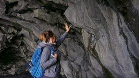 Woman exploring cave on Reynisfjara beach near Vik, Icealnd stock footage